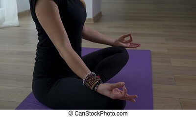 Woman sitting in meditation lotus pose in a yoga gym