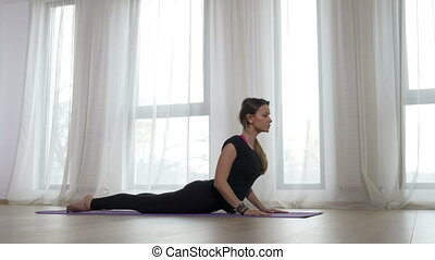 Young blonde adult woman doing bow pose during yoga workout