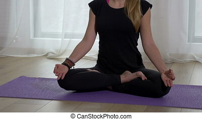 Beautiful adult female meditating in lotus pose in a yoga...