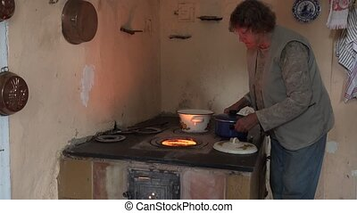 Senior countrywoman cooking in pots on old furnace stove...