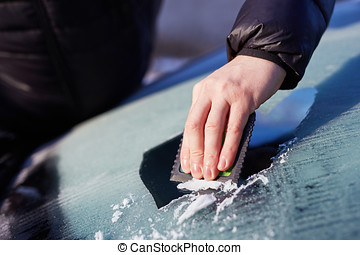 Close up of man scraping ice from the windshield of a car
