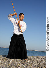Serious man exercising aikido - Serious man in kimono with...