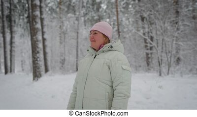 adult woman with blonde hair, which are hidden under the pink hat, wearing a white winter jacket, standing in the middle of snow-covered pine forest and enjoys beautiful frosty  day