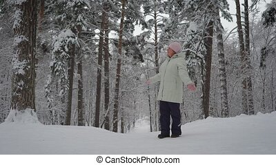 The adult woman in the winter wood. The pensioner enjoys the...