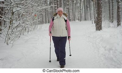 Active woman in warm clothes doing nordic walking in the...