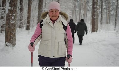 Sport adult woman with rosy cheeks wearing a pink hat and  sweater,  white vest  black sweat pants  engaged in race walking,  along  snowy trail in the pine forest. She is happy of good winter weather