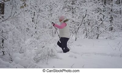 Image of stepping woman picking her way through snowdrifts with ski poles in the forest. Female athlete is doing nordic walking on the path in winter nature with snow-covered trees in the foreground.