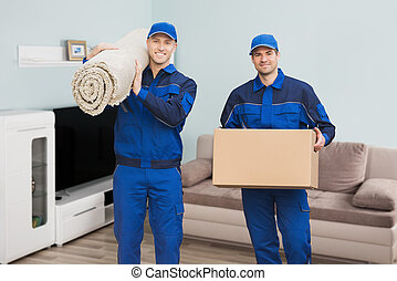 Two Male Movers Standing In House - Portrait Of A Two Male...