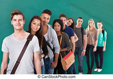 Confident College Students Standing In A Queue - Portrait of...