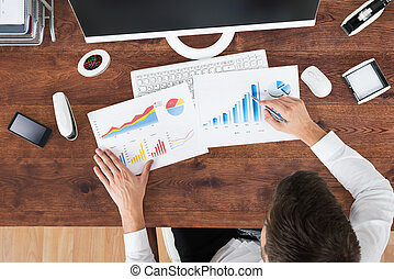 Businessman Analyzing Graph At Office Desk