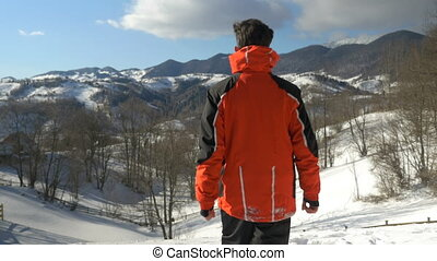 Man making arms raised victory gesture while admiring a winter landscape at the top of the mountains