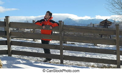 Young man smiling and leaning on a fence in a beautiful winter day at the countryside