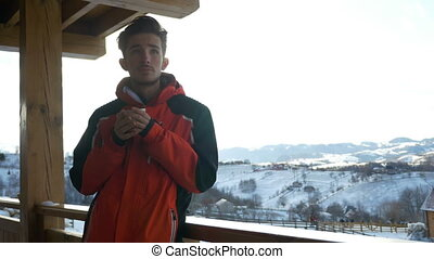 Young man drinking a cup of hot coffee on a deck in winter...