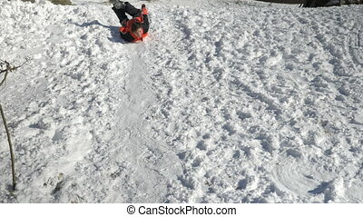 Joyful teen playing sliding in the snow in a sunny winter...