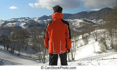 Man enjoying a wonderful sunny day in winter season at the top of the mountains