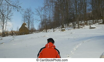 Young man wearing ski costume creating a footpath in the...