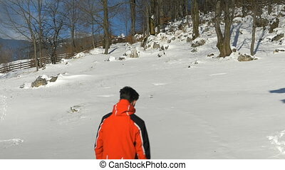 Man walking through the snow wearing a ski costume at the...