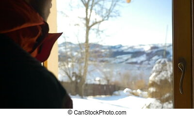 Young man looking out the window at beautiful landscape in winter at the mountains