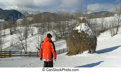 Man walking outside on a mountain at the countryside through the snow along a haystack