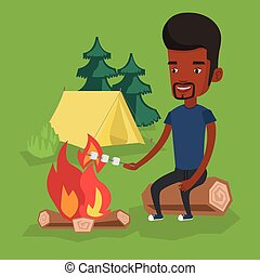 Man roasting marshmallow over campfire. - African-american...