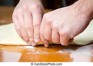 Male baker spreading dough for making pizza - Male baker...
