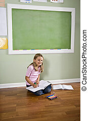 Child sitting on floor writing in classroom