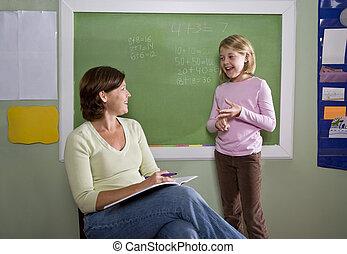 School girl and teacher by blackboard in classroom