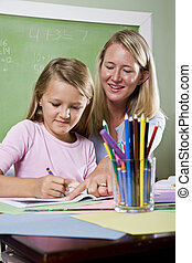 Teacher and young student in class writing - Back to school...