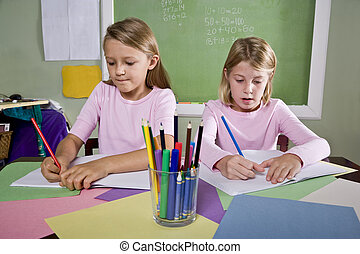 Girls in classroom doing schoolwork, writing - Back to...
