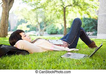 Mixed race college student sleeping on the grass at campus