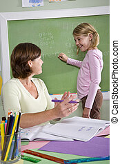 School girl and teacher by blackboard in classroom - Back to...