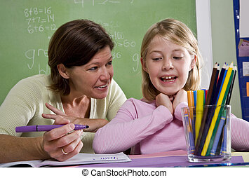 Teacher teaching young student in classroom - Back to school...
