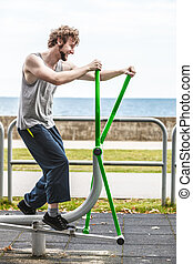 Active man exercising on elliptical trainer. - Active young...