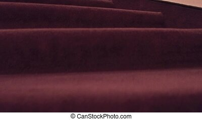 Close-up steadicam shot of old building staircase covered with carpet. 4K clip