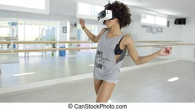 Excited female dancer with VR goggles on eyes. She...