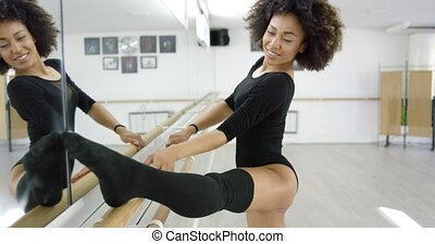 Supple young dancer working out at the bar with her foot...