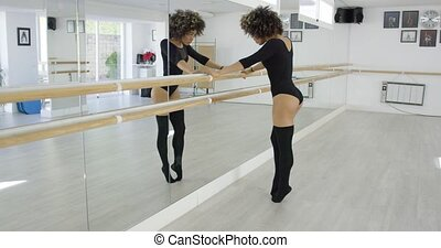 Attractive young dancer practicing at the bar in a bright...