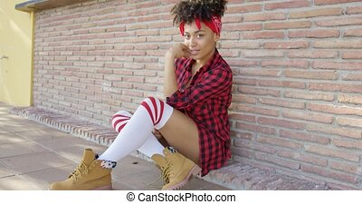 Thoughtful chic young woman sitting on the ground -...