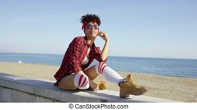 Trendy young woman relaxing on a beachfront wall on a...