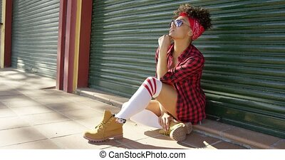 Gorgeous african american girl sitting next to fence -...