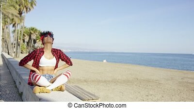 Sexy fashionable young woman at the seaside sitting on a...