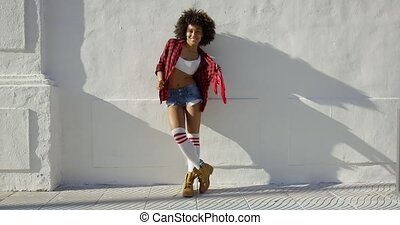 Beautiful fashionable african american girl leaning against...