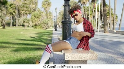 Smiling trendy young woman on a marble bench - Smiling...
