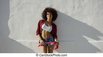 Sexy african american girl with afro haircut leaning against...