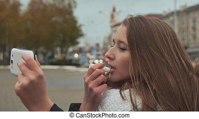 Young beautiful girl lipstick hygienic lipstick on a city...