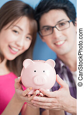 couple hold pink piggy bank - young couple hold pink pig...