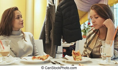 Two young schoolgirls friends eating pizza and talking in a cafe fun. Autumn, Winter.