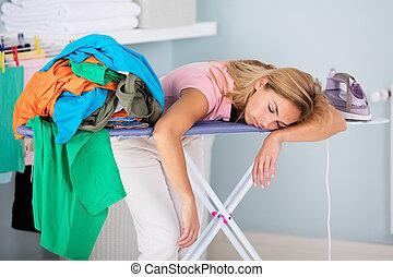 Tired Woman Sleeping On Ironing Board