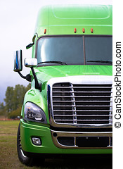 Elegant modern semi truck in green on green parcking lot -...