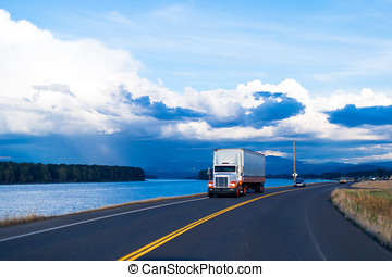 Spectacular river view of road with semi truck and trailer -...